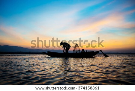 Silhouette of traditional fishermen throwing net fishing inle lake at sunrise time.(The casting people living along the River) - stock photo