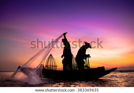 Silhouette of traditional fishermen throwing net fishing lake at sunrise time. Thailand.(The casting people living along the River) - stock photo