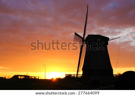 Silhouette of traditional windmill in Netherlands during sunrise - stock photo