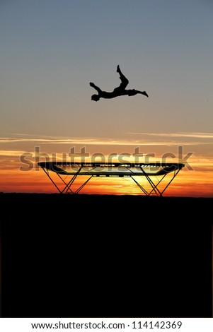 silhouette of trampoline gymnast in sunset - stock photo