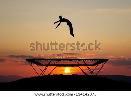 silhouette of trampoline gymnast in sunset