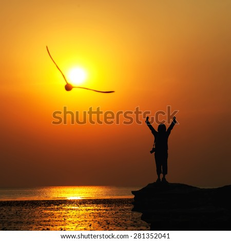 Silhouette of traveller with hands raised to birds flying in to the sun at  sunset. - stock photo