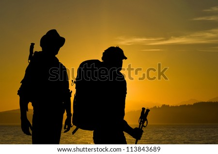 Silhouette of two adventurers admiring the radiant sunset over a lake with hills and forests in the background - stock photo