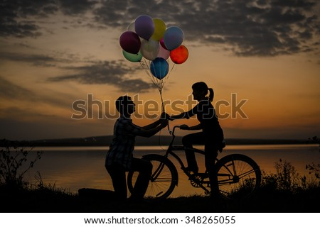 Silhouette of two beautiful couple Man sitting at one bicycle Woman holding give colorful balloons on sunset sky on Water in lake background Copy space for inscription Pair on date Birthday party - stock photo
