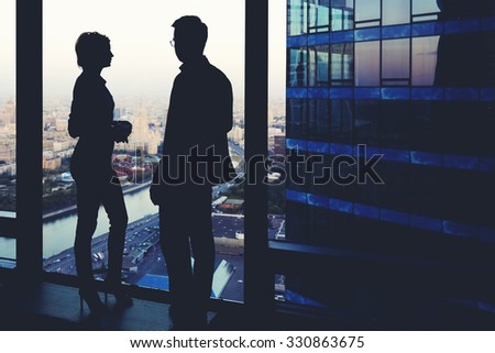 Silhouette of two business partners having conversation while standing near skyscraper window in modern interior with cityscape on background, young colleagues discuss ideas while rest after meeting  - stock photo