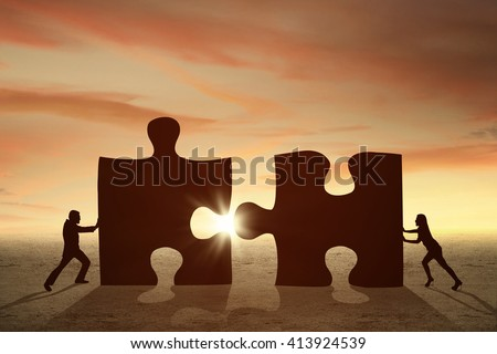 Silhouette of two businesspeople assemble two big jigsaw at sunset time