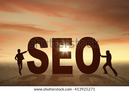 Silhouette of two businesspeople pushing a SEO word at sunset time