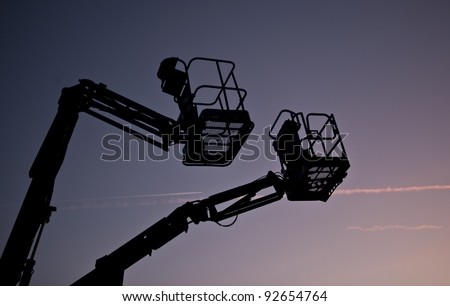 Silhouette of two cherry pickers against the evening sky - stock photo