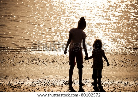 Silhouette of two children on sea beach
