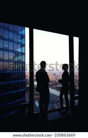 Silhouette of two confident colleagues having conversation while standing in corridor big company near window in evening time, young skilled workers discuss ideas after business meeting with partners - stock photo