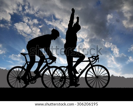 Silhouette of two cyclists riding a road bike at sunset - stock photo