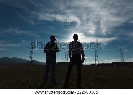 silhouette of two engineers standing at  electricity station - stock photo