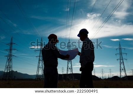 silhouette of two engineers standing at electricity station, discussing plan - stock photo