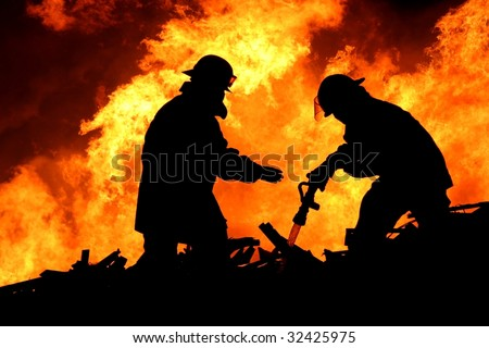 Silhouette of two firemen fighting a huge fire of burning timber - stock photo