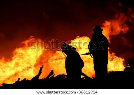 Silhouette of two firemen fighting a raging fire with huge flames of burning scrap timber - stock photo