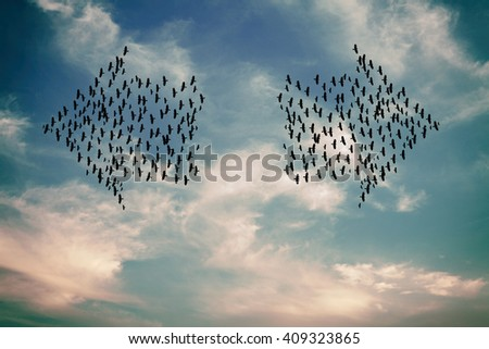 Silhouette of two flocks of bird flying in arrow formation towards two direction against a surreal cloudy sky.