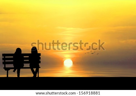 Silhouette of two friends sitting on wood bench near beach staring at flying bird - stock photo