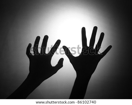Silhouette of two hands behind a glass