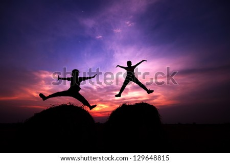 Silhouette of two happy children jumping at once during sunset - stock photo