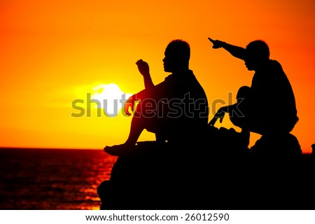 silhouette of two man talking at sunset