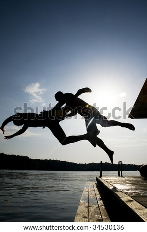 Silhouette of two men jumping into a lake at the same time
