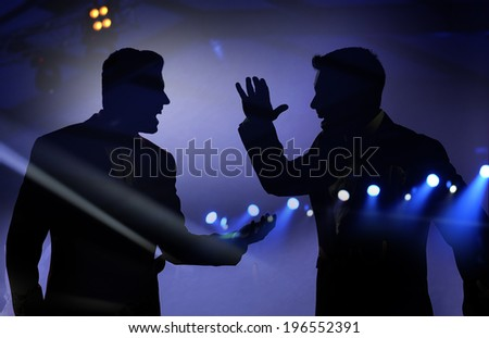 Silhouette of two men on the stage.
