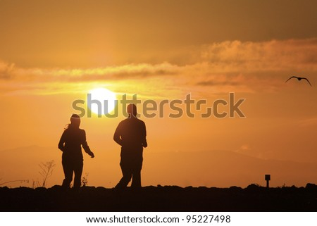 silhouette of two people running in the early morning with sun shinning - stock photo