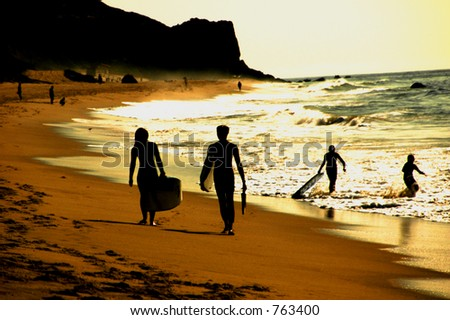 Silhouette of two surfers walking on beach, people playing in background.- soft focus - stock photo