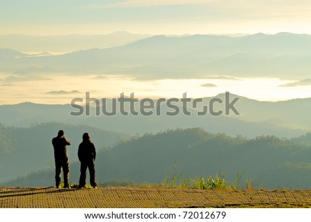 Silhouette of two tourists looking at the beautiful view of mountains in fog at dawn; Tourist attraction point in Maehongson, the north of  Thailand - stock photo