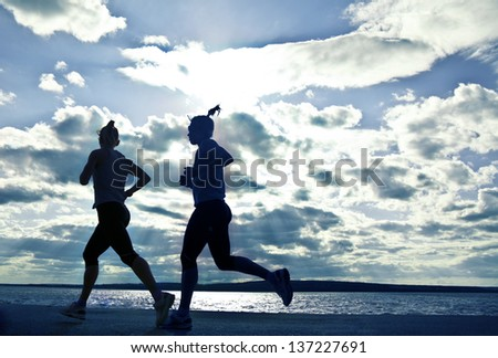 silhouette of two women running at sunset or sunrise Two phases of motion of a girl - stock photo