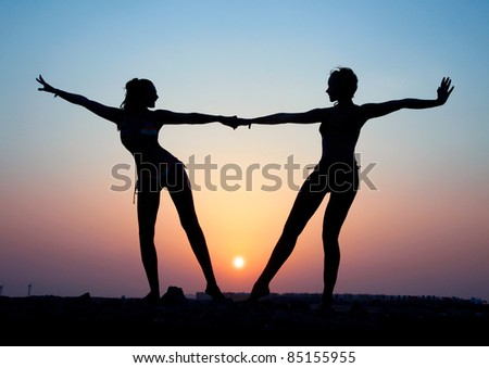 Silhouette of two young women against the evening sunset - stock photo
