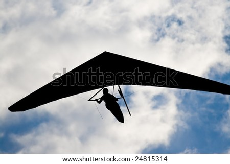 Silhouette of unrecognizable hangglider pilot in the blue sky