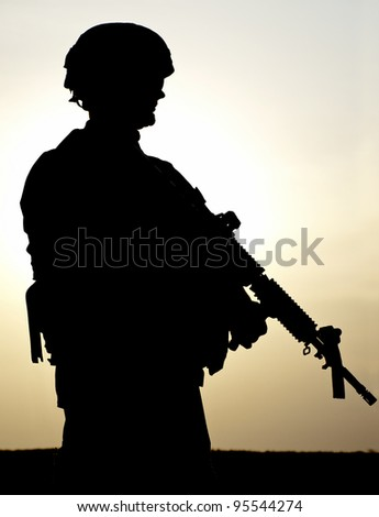 Silhouette of US soldier with rifle against a sunset - stock photo