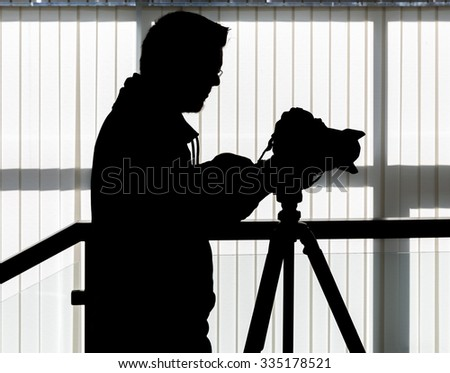 Silhouette of video and photographic equipment on a tripod at the workplace indoors. Photographer in the background - stock photo