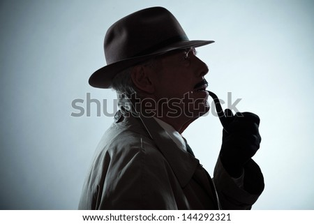 Silhouette of vintage detective with mustache and hat. Smoking pipe. Studio shot.