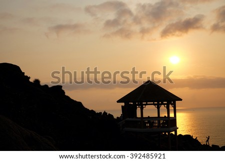 Silhouette of watch tower and people in morning at Dai Lanh cape, Mui Dien, Phu Yen, Viet Nam, yellow sun in sunrise make beautiful scene, this place catch the first sunlight in Vietnam country