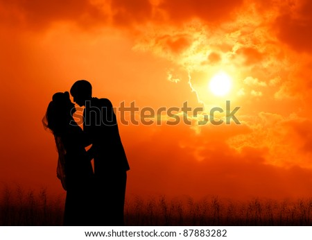 silhouette of wedding couple at sunrise - stock photo