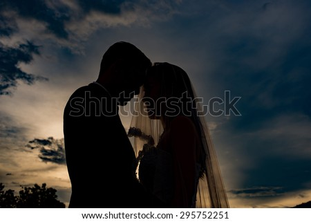 silhouette of wedding couple in beautiful sunset,Romantic silhouette of wedding couple at sunset - stock photo