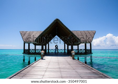 Silhouette of wedding couple in wooden bower. Tropical place