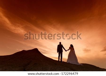 Silhouette of wedding couple with the red sunset