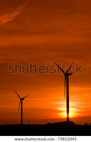 Silhouette of wind power station at sunset - stock photo