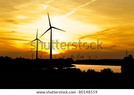 Silhouette of wind turbine farm over sunset - stock photo