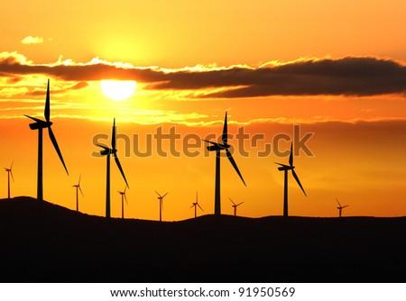 Silhouette of wind turbine farm over sunset - stock photo