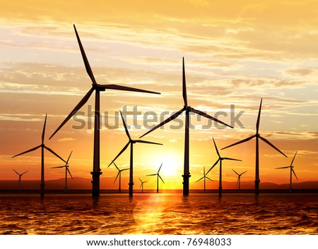 silhouette of wind turbine generating electricity on sunset - stock photo