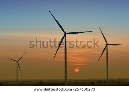 Silhouette of 3 Wind Turbine with sun rise in the orange and blue background.