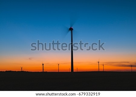 Silhouette of wind turbines during colorful summer sunset