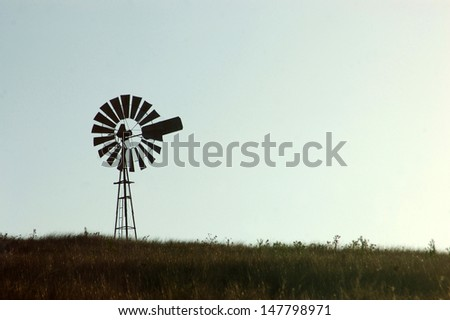 Silhouette of windmill in paddock, Queensland, Australia. Windmills are commonly used for pumping water from bores or dams to troughs for livestock. - stock photo