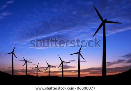 Silhouette of windmills on blue sky background with space