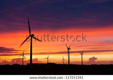 Silhouette of windturbines on an amazing sunset - stock photo