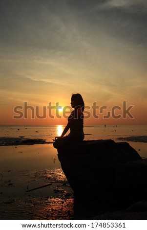 Silhouette of woman act meditation yoga on the rock with sea sunset background